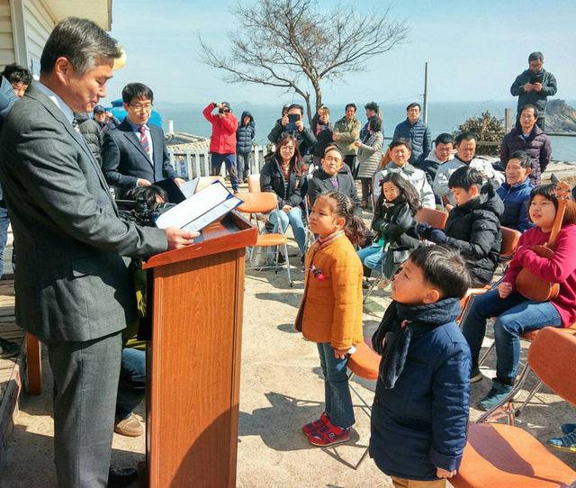 Hiệu trưởng Trường tiểu học Cheongpa, ông Lee Min-cheol, trao giấy nhập học cho cậu bé Ryu Chan-hee (bên phải) và cho một cô bé khác vào học điểm trường khác trên đảo Hodo tại buổi lễ nhập học ngày 3/3/2017. (Ảnh:Hankook Ilbo)