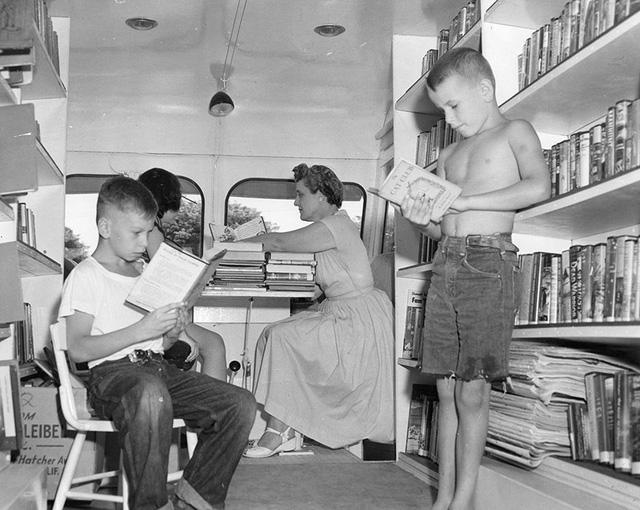 """Hai cậu bé đang đọc """"ngấu nghiến"""" những cuốn sách yêu thích bên trong một thư viện lưu động. Ảnh chụp hồi thập niên 1920."""