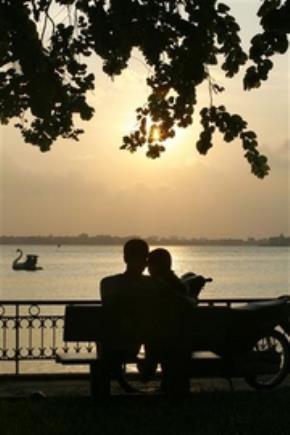 Một đôi trai gái ngồi bên hồ Tây, đường Thanh Niên. Ảnh: Reuters.