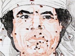 Lỗ chỗ vết đạn trên tranh vẽ ông Moammar Gadhafi trên tường một tòa nhà ở Tripoli. Ảnh: AP
