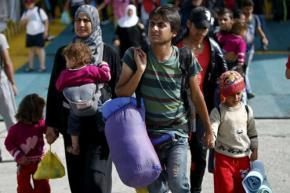 Một gia đình tị nạn Syria xuống tàu ở Hy Lạp hôm qua. Ảnh: Reuters