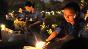 Các bạn đoàn viên, thanh niên TP.HCM thắp nến tri ân tại phần mộ các anh hùng liệt sĩ ở nghĩa trang liệt sĩ TP.HCM tối 26-7 - Ảnh: Minh Đức