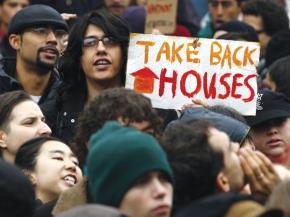 Những người biểu tình của phong trào Chiếm phố Wall đang phản đối bên ngoài một ngôi nhà bị tịch biên, ở khu Đông New York của Brooklyn, thành phố New York hôm 6.12. Những người biểu tình đồng loạt trong một ngày tại nhiều thành phố...