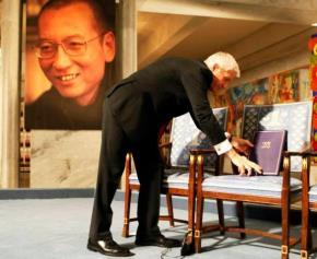Chủ tịch Ủy ban Nobel của Na Uy bên chiếc ghế trống cùng tấm bằng và huy chương Nobel Hòa bình dành cho Lưu Hiểu Ba