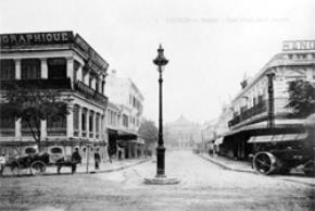 """Đường Tràng Tiền đầu thế kỷ XX, phía xa là Nhà Hát Lớn, toà nhà bên trái là trụ sở một tờ báo lớn và nhà in của """"ông tổ ấn loát và nhà in ở Việt Nam"""" H.Schneider"""