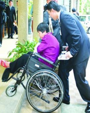 Một doanh nhân đang giúp người khuyết tật di chuyển trên xe lăn trong chương trình tặng xe lăn cho người khuyết tật do Hội Bảo trợ bệnh nhân nghèo TPHCM tổ chức. Ảnh: Lê Toàn.